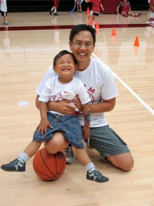 Happy father and son kneeling on a basketball court