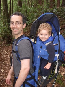 Father hikes with son in a backpack carrier