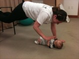 Mom gives high five to infant while doing a plank